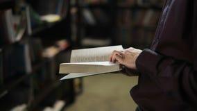 Estudante que lê um livro na biblioteca Conceito da instrução vídeos de arquivo