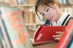 Estudante que lê um livro na estante Imagens de Stock Royalty Free