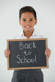 Estudante que mantém a ardósia da escrita com texto de volta à escola contra o fundo branco Fotos de Stock