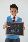 Estudante que mantém a ardósia da escrita com texto de volta à escola contra o fundo branco Imagens de Stock