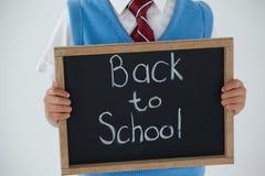 Estudante que mantém a ardósia da escrita com texto de volta à escola contra o fundo branco Foto de Stock Royalty Free