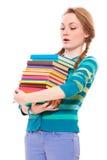 Estudante que olha à pilha dos livros Fotografia de Stock