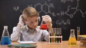 Estudante que olha o líquido vermelho na garrafa e que risca a cabeça, não tendo nenhuma ideia filme