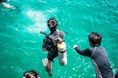 Estudante que prepara-se para saltar no mar para o mergulhador que conduz o exame imagens de stock royalty free
