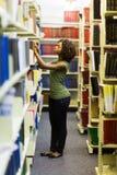 Estudante que procura o livro fotografia de stock