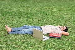 Estudante que relaxa no terreno imagem de stock