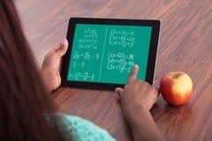 Estudante que resolve problemas de matemática na tabuleta digital Foto de Stock Royalty Free
