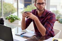 Estudante que senta-se em uma mesa com café em suas mãos Imagens de Stock