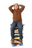 Estudante que senta-se em uma pilha dos livros Fotos de Stock