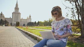 Estudante que trabalha com um portátil em um quadrado no fundo da universidade estadual de Lomonosov Moscou filme