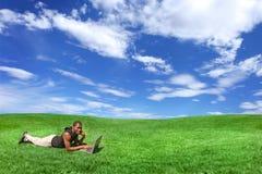 Estudante que trabalha em um computador ao ar livre em um Beauti foto de stock royalty free