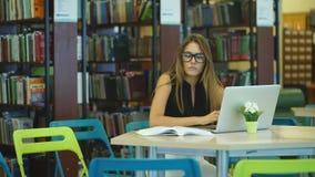 Estudante que trabalha em um computador na biblioteca junto com livros video estoque