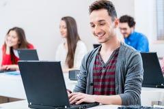 Estudante que trabalha no PC do portátil na faculdade Fotos de Stock Royalty Free
