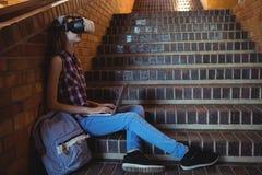 Estudante que usa auriculares e portátil da realidade virtual na escadaria foto de stock royalty free