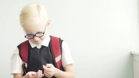 A estudante retira de seu bolso do ` das calças uma bolsa pequena filme
