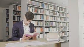 Estudante sério que procura a informação no livro na biblioteca filme
