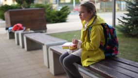 Estudante s? da menina que senta-se em um banco perto da escola Passagem dos povos perto A crian?a fricciona nervosamente seus vi video estoque