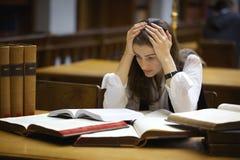 Estudante sobrecarregado na biblioteca Fotos de Stock