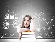 Estudante sonhador com uma pilha dos livros, gráficos Foto de Stock Royalty Free