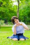 A estudante tailandesa bonito está sentando-se na grama e está fazendo-se o sym do coração Fotografia de Stock Royalty Free