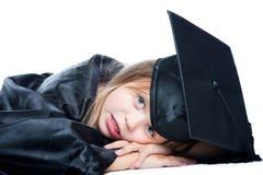 Estudante Tired no vestido da graduação em w isolado Imagem de Stock