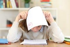 Estudante triste com um exame falhado em casa imagens de stock royalty free