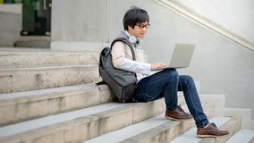 Estudante universitário asiática do homem que usa o portátil na escada imagem de stock royalty free
