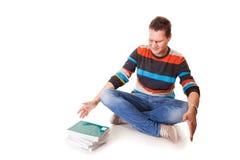 Estudante universitário cansado com a pilha de livros que estuda para exames  Imagens de Stock