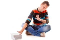 Estudante universitário cansado com a pilha de livros que estuda para os exames isolados Foto de Stock