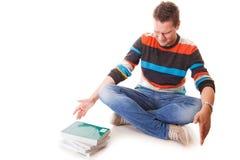 Estudante universitário cansado com a pilha de livros que estuda para os exames isolados Imagens de Stock Royalty Free