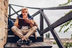 Estudante universitário com o livro de leitura da trouxa que anda no parque do outono que senta-se em escadas foto de stock royalty free