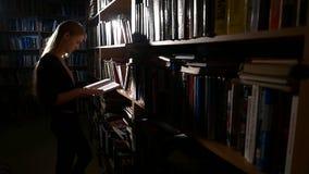 A estudante universitário consideravelmente nova em uma biblioteca, escolhe vídeos de arquivo