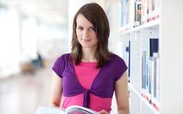 Estudante universitário consideravelmente novo em uma biblioteca Imagem de Stock Royalty Free
