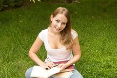 Estudante universitário de sorriso que lê um livro fotografia de stock