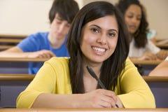 Estudante universitário fêmea que escuta uma leitura Fotografia de Stock Royalty Free
