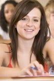 Estudante universitário fêmea que escuta uma leitura Imagem de Stock