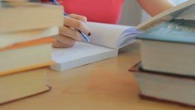 Estudante universitário fêmea que prepara o exame e que lê um livro e que escreve notas video estoque