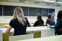 Estudante universitário fêmea que senta-se em uma sala de aula Imagens de Stock
