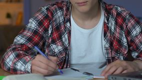 Estudante universitário feliz que mostra os polegares acima, sentando-se na mesa dos trabalhos de casa, conhecimento vídeos de arquivo