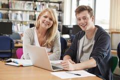 Estudante universitário Has Individual Tuition do professor In Library imagens de stock