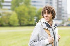 Estudante universitário masculina nova de sorriso no terreno da faculdade imagens de stock royalty free