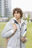 Estudante universitário masculina nova que guarda livros de texto no terreno Fotos de Stock