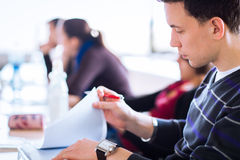 Estudante universitário masculino novo, considerável que senta-se em uma sala de aula completamente Fotos de Stock