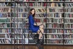 Estudante universitário nova bonita que senta-se em escadas na biblioteca, trabalhando no portátil Mulher que veste o vestido azu fotos de stock