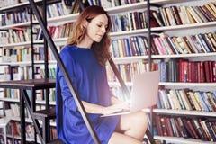 Estudante universitário nova bonita que senta-se em escadas na biblioteca, trabalhando no portátil Mulher que veste o vestido azu fotos de stock royalty free