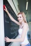 Estudante universitário que apaga o quadro Fotografia de Stock