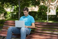 Estudante universit?rio do homem novo que aprende em linha atrav?s do laptop, sentando-se em um banco em um terreno fotos de stock