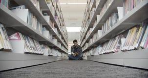 Estudante universit?rio que senta-se no assoalho na biblioteca, livro de leitura filme