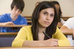 Estudante universitário fêmea que escuta uma leitura Fotos de Stock