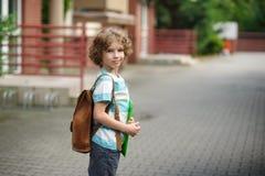 A estudante vai à escola com uma sacola atrás dos ombros imagem de stock